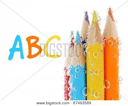 Colorful pencils in water with bubbles, isolated on white
