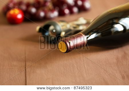 Bottle of red wine with grape on wooden background