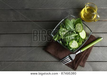 Glass bowl of green salad with cucumber and spinach on wooden table, top view