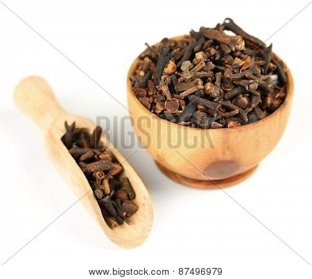 Clove spice in wooden bowl, isolated on white