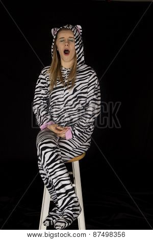Young Female Model Wearing Cat Pajamas Yawning And Sitting On Stool