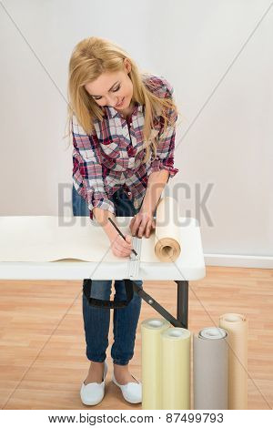 Woman Taking Measurement Of Wallpaper