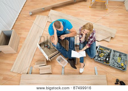 Thoughtful Couple With Disassembled Furniture