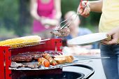 stock photo of frazzled  - Woman dishing out tasty grilled chuck steak - JPG