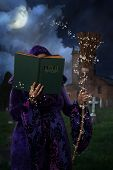 picture of graveyard  - Woman wearing purple cloak in graveyard with book of magic spells and broomstick - JPG