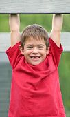 pic of swingset  - boy hanging from swingset with a big smile on face - JPG