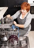 stock photo of dishwasher  - Woman folding the dishes in the dishwasher - JPG