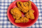 stock photo of fried chicken  - Four pieces of fresh fried chicken on a plate and blue plaid towel - JPG