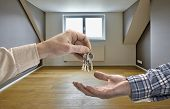 picture of possess  - Realtor giving house key to buyer in empty room - JPG