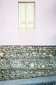 image of basement  - The old window with white closed shutters on an old house with stone basement - JPG