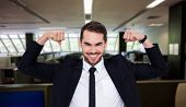 stock photo of united we stand  - Happy businessman in suit cheering against empty office with separate units - JPG