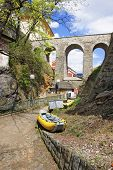 stock photo of raft  - Yellow air rafts under the stone bridge in city of Cesky Krumlovin spring - JPG