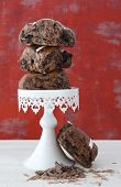 stock photo of cake stand  - Stack of Chocolate Fruit Buns on White Cake Stand on white shabby chic wood table with red wallpaper background - JPG