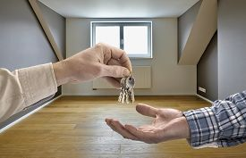 picture of possession  - Realtor giving house key to buyer in empty room - JPG