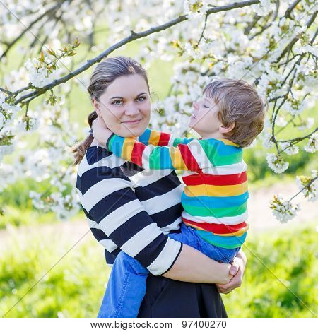 Young Mother And Little Kid Boy In Blooming Garden