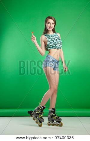 Very attractive woman with lollipop posing on green studio background wearing  rollerskates