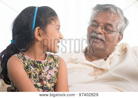 Portrait of Indian family at home. Grandparent and grandchild having conversation. Asian people living lifestyle. Grandfather and granddaughter.