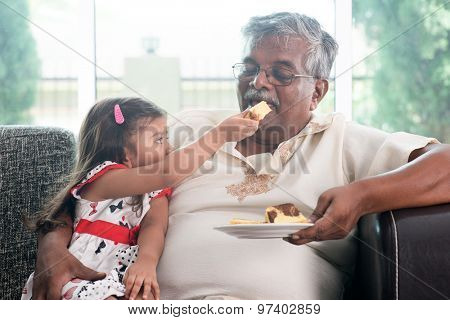 Portrait of Indian family at home. Grandchild feeding butter cake to grandparent. Grandfather and granddaughter. Asian people living lifestyle.