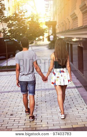 Young couple walking through the city holding hands