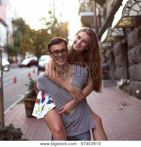 Girl riding a guy in the street of a large city beautiful