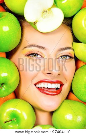 Close-up portrait of a beautiful smiling woman among fresh green apples. Healthy eating concept. Make-up, cosmetics. Healthy teeth.