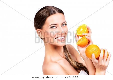 Pretty joyful young woman holding fresh juicy oranges. Healthy lifestyle. Healthy eating. Fruits and vegetables. Isolated over white.