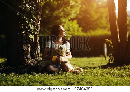The girl with dog sit on a grass
