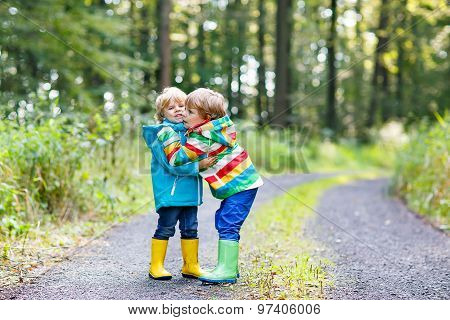 Two Little Sibling Boys In Colorful Raincoats And Boots Walking