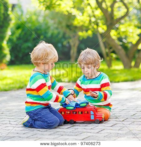 Two Siblings, Kid Boys Playing With Red Wooden Toy