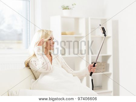 Beautiful woman taking selfie with a stick in the morning.
