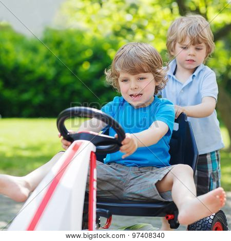 Two Funny Little Boys Having Fun With Race Car Outdoors