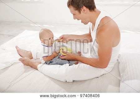 Young father with his nine months old son on the bed at home