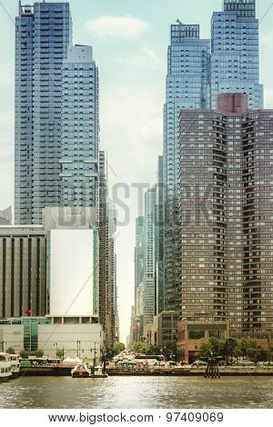 An image of some high rise buildings in New York with an advertising wall
