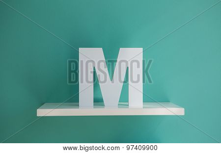 Letter M turquoise color on a white shelf.