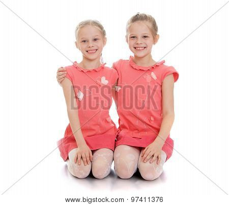 Girls sisters sit on the floor