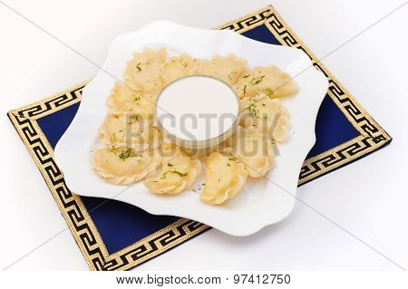 Varenyky, dumplings or pirogi, with sour cream and greens on white plate