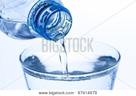 Pouring Water In An Elegant Glass Water Drops On White Background. Macro