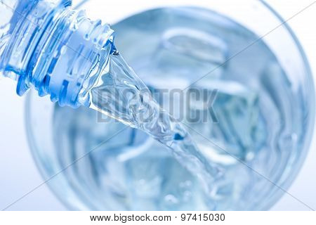 Pouring Water In An Elegant Glass With Ice And Water Drops. Macro