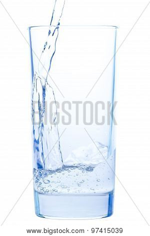 Pouring Water In An Elegant Glass And Water Drops On White Background