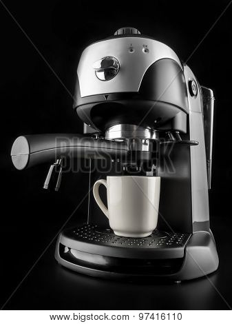 Modern coffee machine with white mug shot on black background