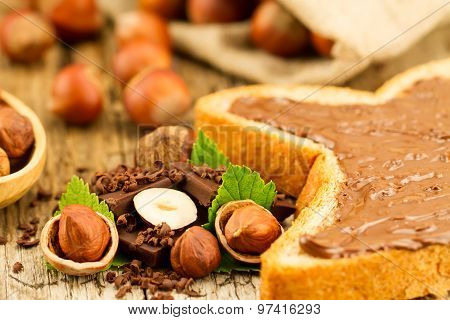 Hazelnut With Chocolate, Toast And Green Leaves On Old Wooden Background
