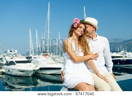 Attractive Young Couple Walking Alongside The Marina With Moored Boats On A Luxury Waterfront