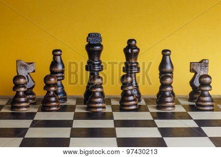 Wooden Chess Set Yellow Background.