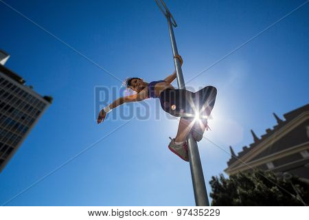 Athletic woman hanging on street sign in the city