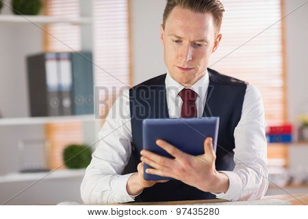 Focused businessman using his tablet pc in his office