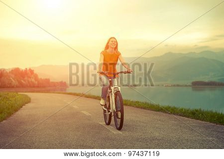 Happiness woman on the bicycle outdoor.