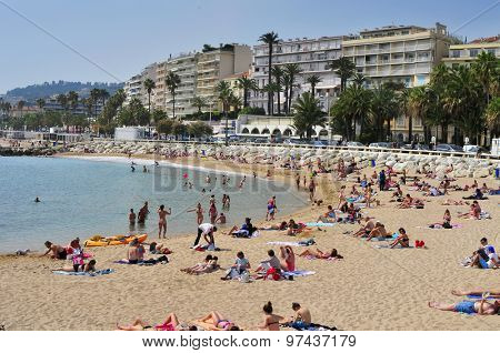 CANNES, FRANCE - MAY 14: Sunbathers at the public beach at the end of the Promenade de la Croisette on May 14, 1015 in Cannes, France. This promenade is famous because of the Cannes Film Festival
