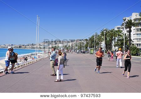NICE, FRANCE - MAY 16: Tourists and joggers in the seafront on May 16, 2015 in Nice, France. The long and famous seafront of Nice bordering the Mediterranean Sea is known as the Promenade des Anglais