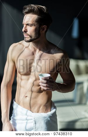 Handsome, Muscular, Young Man Drinking His Morning Coffee In A Hotel Room Standing Next To A Window