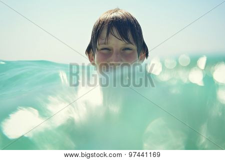 little boy swimming in sea with clean turquoise water transparent, image toned